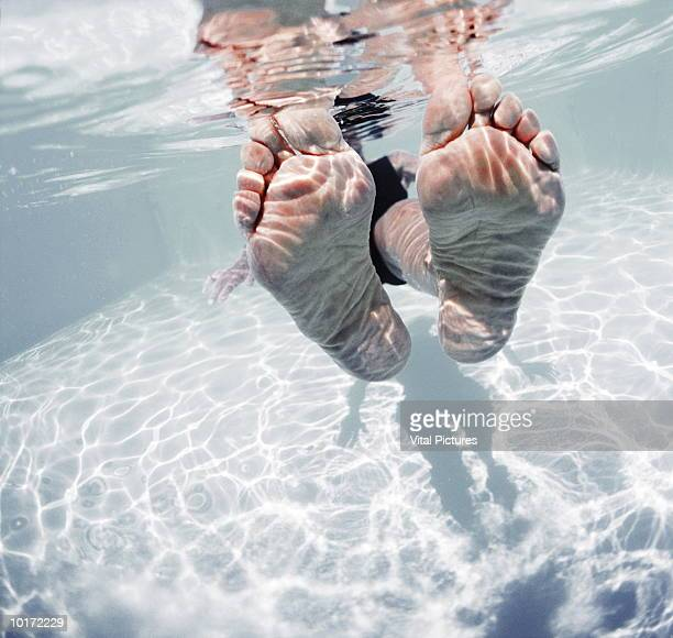 mature womans feet in pool, close-up - female feet soles stock photos and pictures