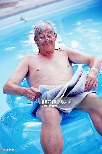 MATURE MAN FLOATING ON POOL