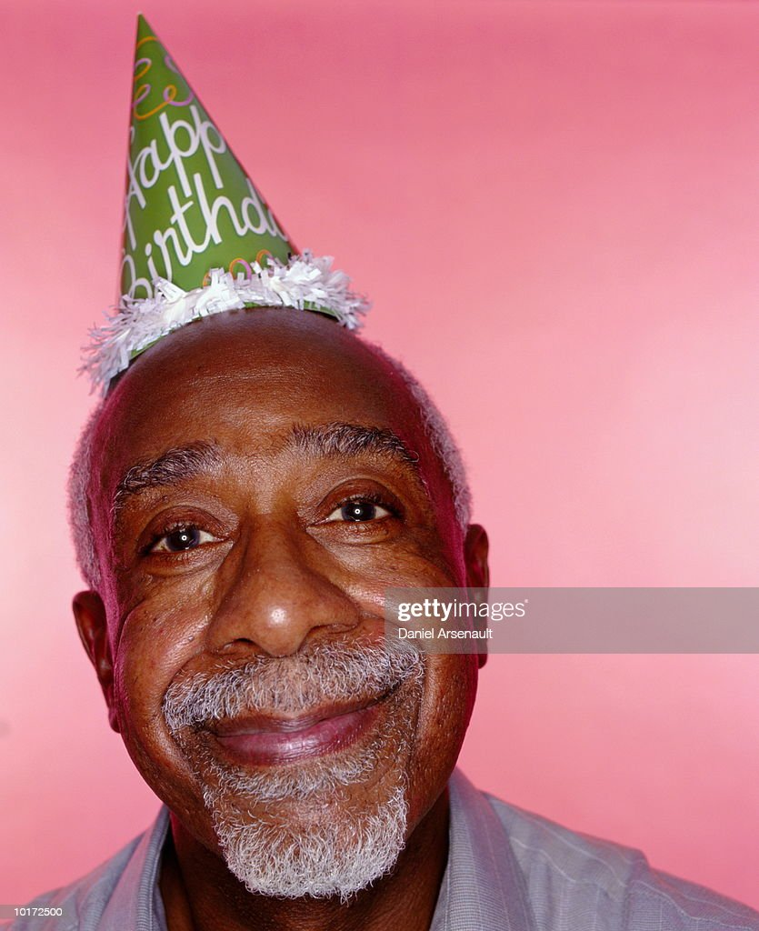 mature black man wearing birthday hat stock photo | getty images