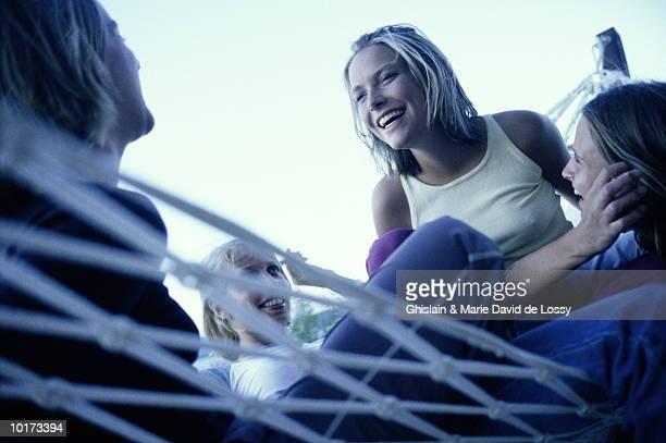 YOUNG WOMEN TALKING, SITTING IN HAMMOCK