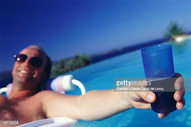 MAN RELAXING IN POOL, HOLDING DRINK