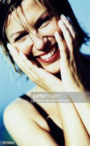 YOUNG WOMAN SMILING, HANDS ON FACE