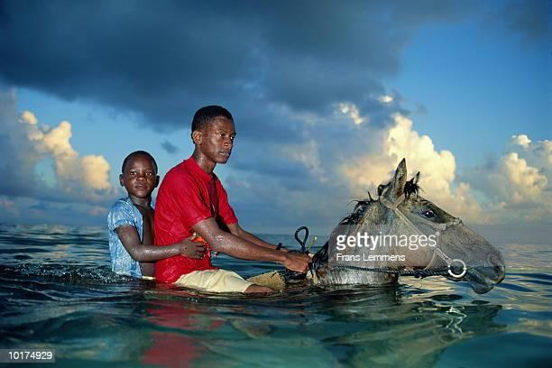 TWO BOYS ON HORSEBACK, IN OCEAN, PUERTO LIMON, COSTA RICA