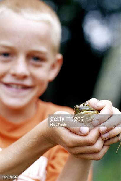 boy holding a frog - ugly kids stock photos and pictures