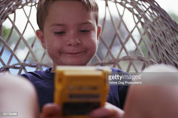 BOY PLAYING WITH HAND HELD GAME