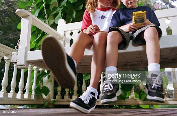 BOY & GIRL SITTING ON BENCH WITH HAND GAME
