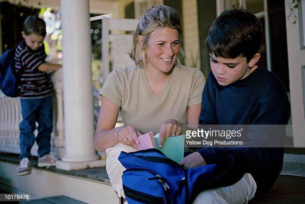 MOTHER PACKING SONS BAG, OTHER SON IN BACKGROUND