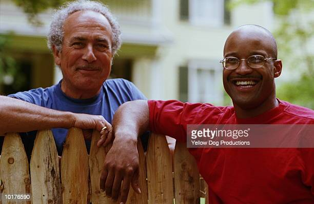 TWO MEN (NEIGHBOURS) STANDING BY FENCE