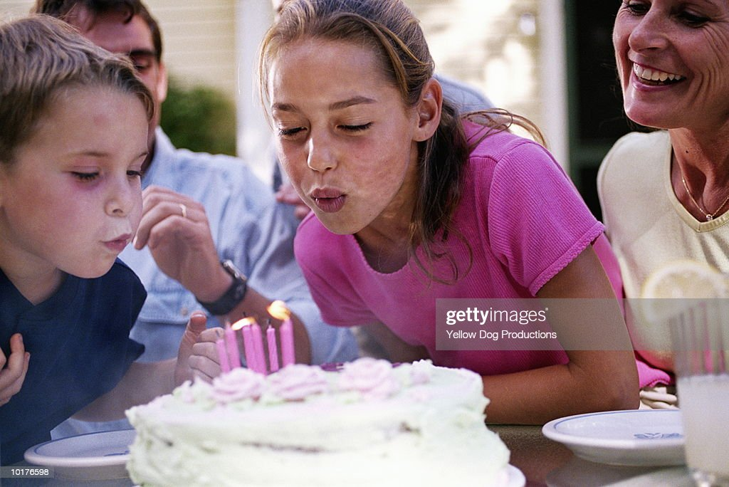 2 KIDS BLOWING OUT CANDLES ON CAKE : Stock Photo