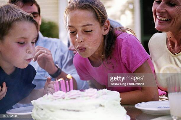 2 kids blowing out candles on cake - girl blows dog stock photos and pictures