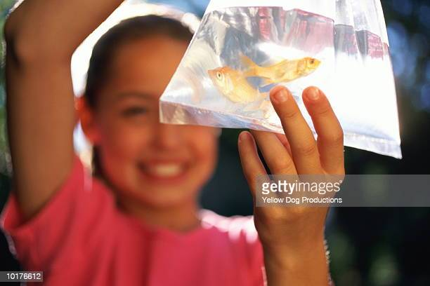 GIRL WITH GOLDFISH IN PLASTIC BAG