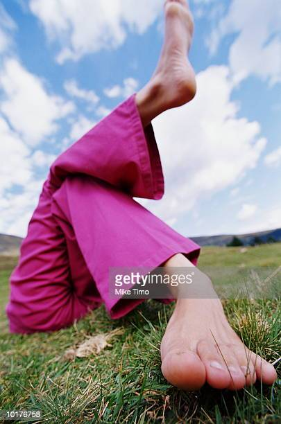 GIRL LYING ON MEADOW WITH LEGS CROSSED