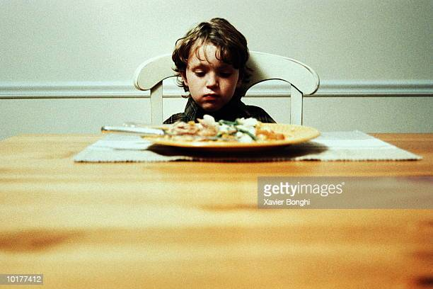 BOY ALONE AT DINNER TABLE, NOT EATING