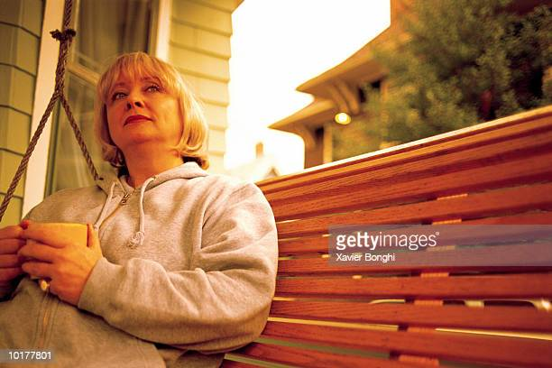 MATURE WOMAN ON PORCH SWING