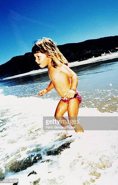 girl (5 to 7) paddling in sea - cross processed stock pictures, royalty-free photos & images