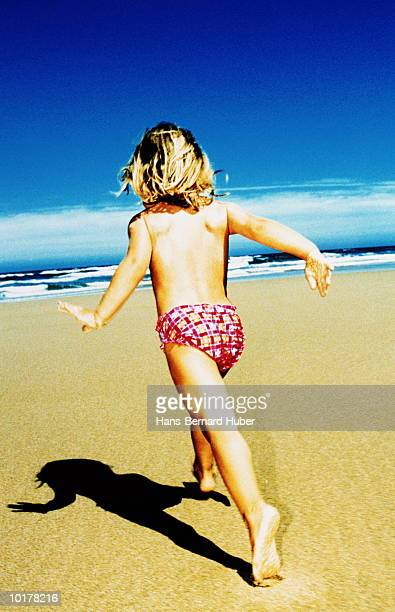 girl (5 to 7) running on beach, rear view - cross processed stock pictures, royalty-free photos & images