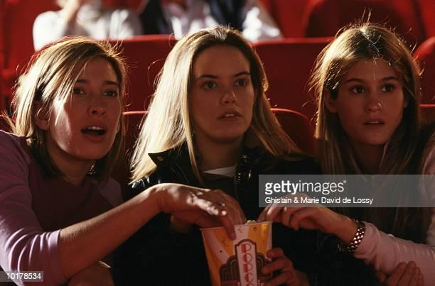 teenage girls  watching film, eating popcorn - alleen tienermeisjes stockfoto's en -beelden