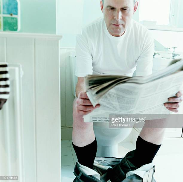 man reading newspaper sitting on toilet - men taking a dump stock pictures, royalty-free photos & images