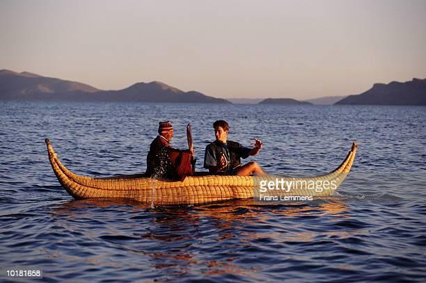 AYMARA INDIAN AND TOURIST CANOEING, LAKE TITICACA, BOLIVIA