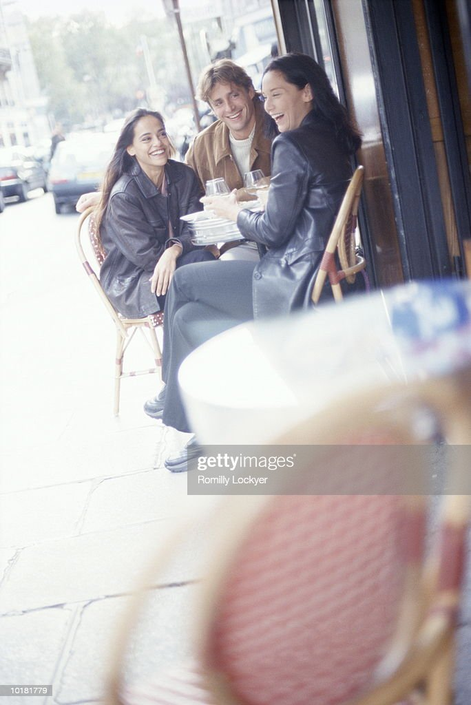 YOUNG PEOPLE SMILING AT OUTDOOR CAFE : Stock Photo