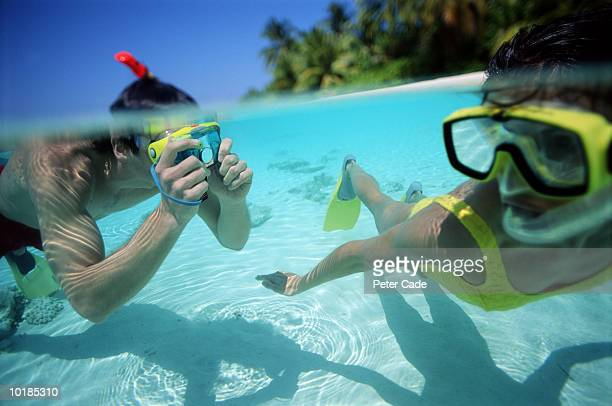 MAN TAKING PHOTOGRAPH OF WOMAN UNDERWATER