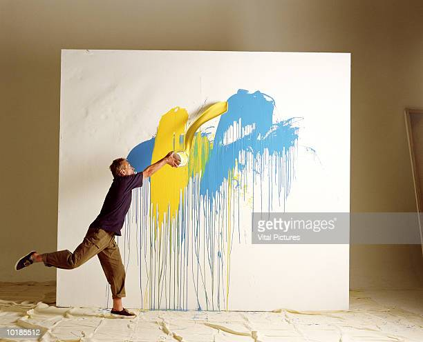 artist throwing paint at canvas - dipinto foto e immagini stock