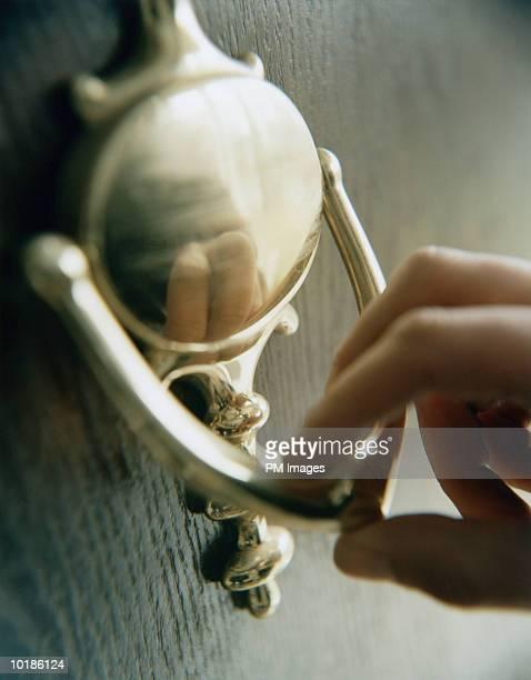 hand on door knocker - knocking on door stock photos and pictures