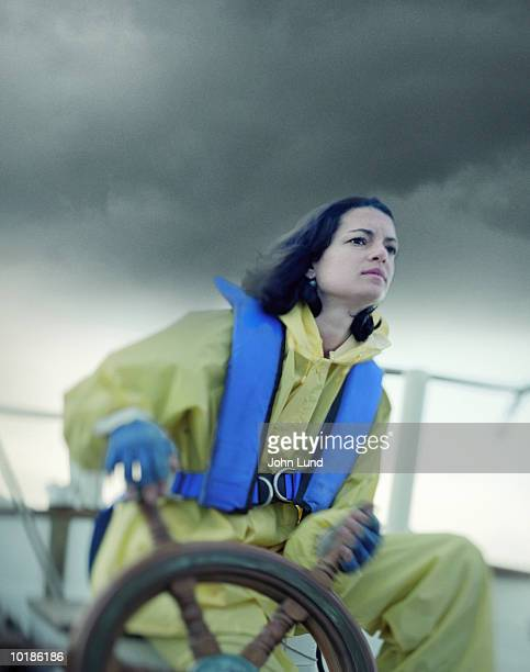 WOMAN NAVIGATING BOAT IN STORM