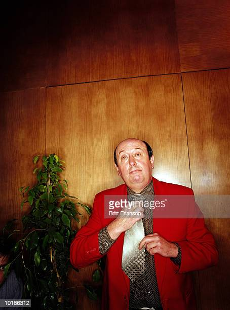 MAN IN RED JACKET ADJUSTING TIE, PORTRAIT