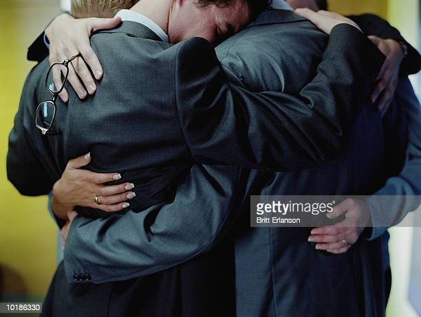 OFFICE COLLEAGUES IN GROUP HUG