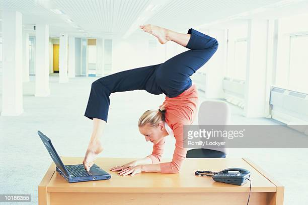 CONTORTIONIST USING LAPTOP COMPUTER WITH FEET