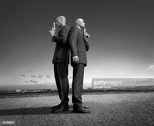 TWO MEN WITH GUNS, STANDING BACK TO BACK, PROFILE (B&W)