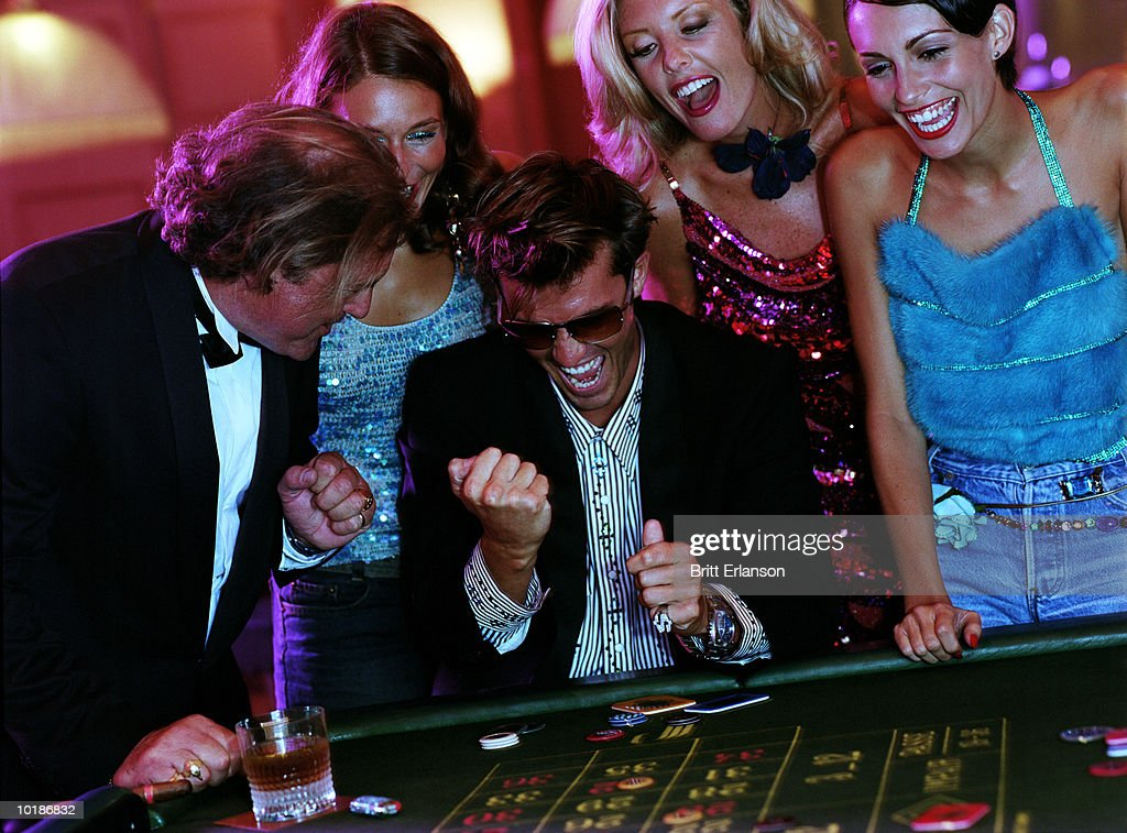 GROUP OF PEOPLE AT ROULETTE TABLE : Stock Photo
