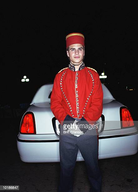 BELLBOY STANDING BY REAR OF CAR, NIGHT