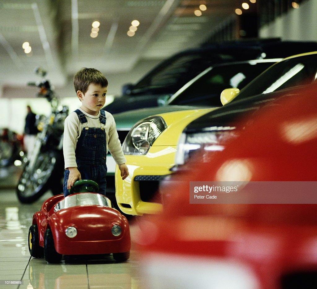 BOY (3-5) WITH TOY CAR IN CAR SHOWROOM : Foto de stock