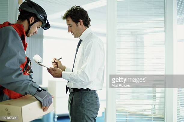 BUSINESSMAN SIGNING FOR PACKAGE FROM COURIER