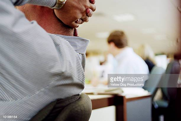 BROKER SITTING BACK WITH HANDS BEHIND HEAD