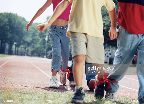 CHILDREN (9-11) IN THREE-LEGGED RACE, CLOSE-UP