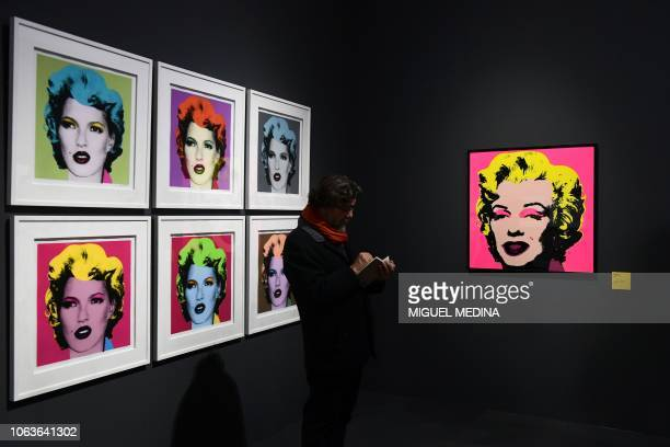 A visitor stands by British street artist Banksy's 2005 silkscreens 'Kate Moss' and US artist Andy Warhol's 1968 silkscreen 'Marilyn Monroe' during a...