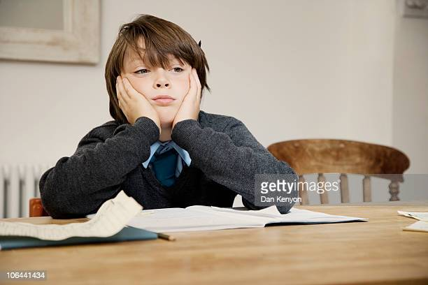 boy sitting at table with homework lokking sad - home schooling stock pictures, royalty-free photos & images