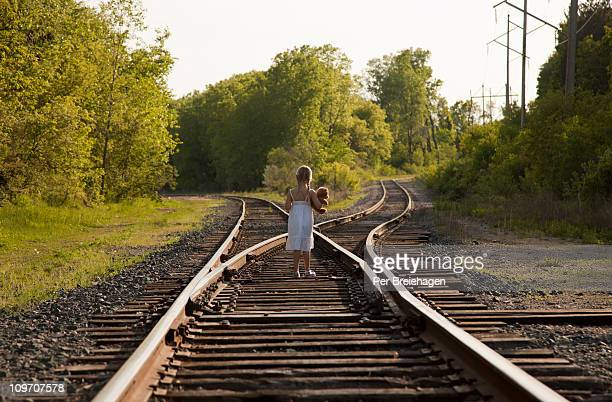 A LITTLE GIRL WITH TOY BEAR AT A  RAILROAD SPLIT