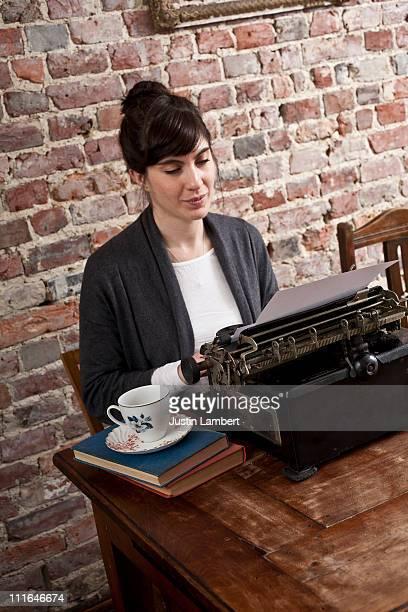 GIRL USING ANTIQUE TYPEWRITER IN CAFE