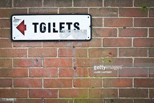 TOILETS SIGN ON BRICK WALL