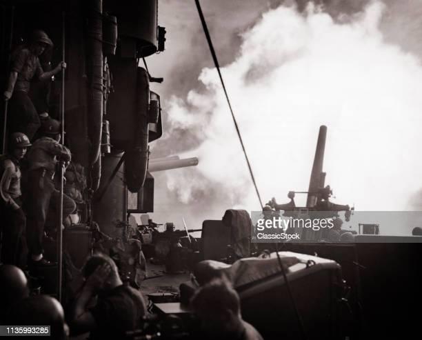 JULY 20 1944 NAVY SHIP CRUISER FIRING GUNS ARTILLERY ISLAND GUAM BOMBARDMENT BATTERY PACIFIC NOISE SAILOR WITH HANDS OVER EARS