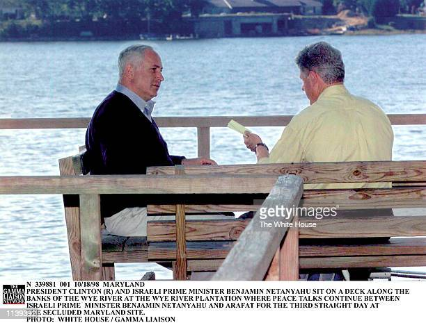 N 339881 001 10/18/98 MARYLAND PRESIDENT CLINTON AND ISRAELI PRIME MINISTER BENJAMIN NETANYAHU SIT ON A DECK ALONG THE BANKS OF THE WYE RIVER AT THE...