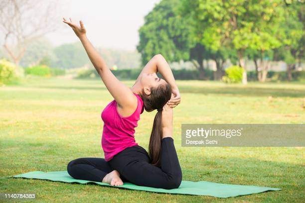 BEAUTIFUL WOMAN PRACTICING YOGA ON GRASSY FIELD AT PARK