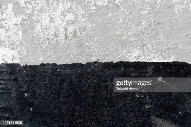 ヒビが入り塗装が剥がれて汚れたコンクリートの壁面写真 - zweifarbig farbe stock-fotos und bilder