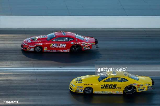 Erica Enders Chevrolet Camaro SS NHRA Pro Stock and Jeg Coughlin Jr Jegs Chevrolet Camaro SS NHRA Pro Stock race down the track during the finals of...