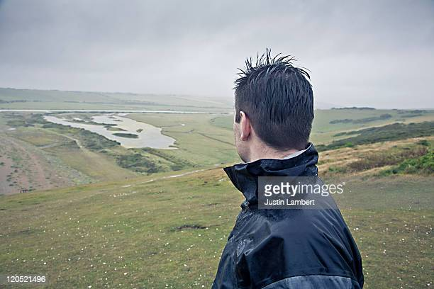 man looks at view on grey rainy day - newpremiumuk stock pictures, royalty-free photos & images