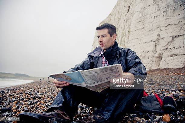 man sits on beach on rainy day looking at map - newpremiumuk stock pictures, royalty-free photos & images